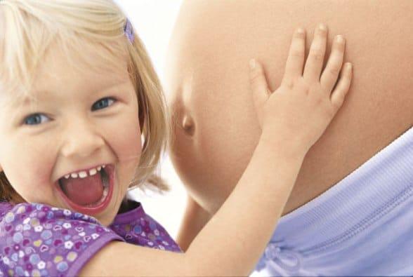 Ребенок обнимает пузо