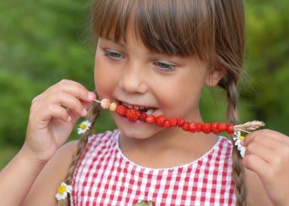 Девочка кушает землянику