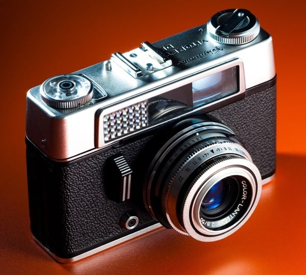 Фотоаппарат на красном фоне