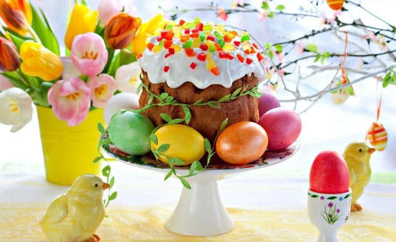 паска, окрашенные яйца и цветы в вазе