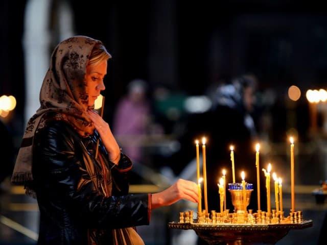 девушка ставит свечку в церкви